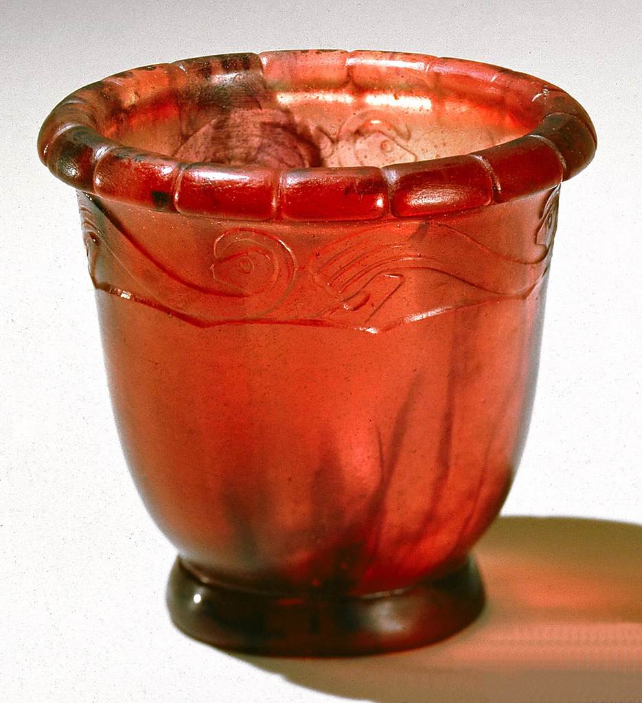 Deep bowl of rose-red glass paste streaked with black; rolled lip with sixteen grooves, low thick foot with scalloped upper edge; beneath lip border of four molded and carved S-wave forms with stylized animal forms between each pair of wave designs, all on a scalloped base line.