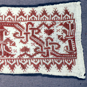 Band fragment showing a faded red geometric pattern on linen.