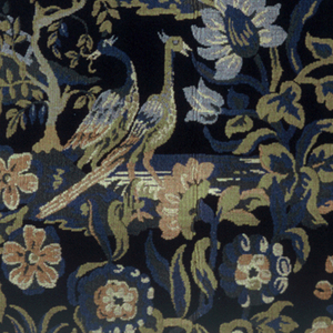Length of upholstery fabric with pair of peacocks standing in water (?) under flowering trees of pale and deep blues, peach, ochre, and shades of green on a black background. Knoll with tree and fence part of same repeat. Woven in imitation of wool needlepoint. Brick repeat of rectangular pattern unit. Woven finish at bottom has two Orinoka Mills symbols.