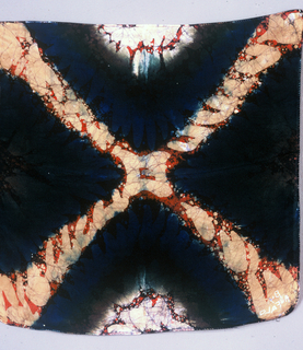 Small square patterned by an X from corner to corner and at the center of each side a half circle. Batik dyed in red and black. Yellow, blue, and green may have been applied by hand to emphasize the X and two opposite half circles.