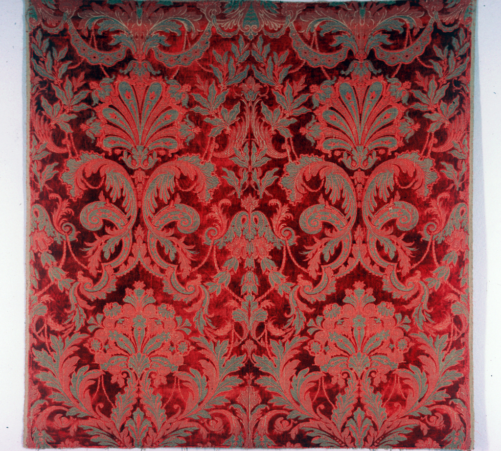 Woven velvet with two side-by-side symmetrical leaf and palmette forms (reversed at center line). Red silk pile in a red foundation with metallic gold supplementary weft patterning.