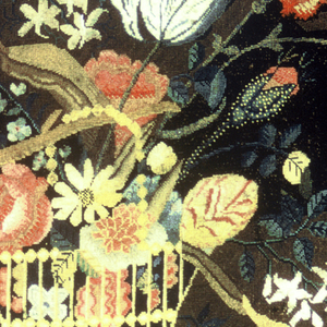 Allover embroidered panel showing a basket filled with naturalistic flowers hanging from a branch of a tree stump growing from a small mound. Three butterflies hover at the top.
