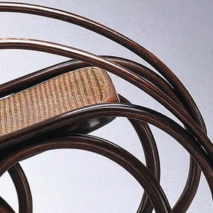 Frame of curving linear bent beechwood elements; the arms flow into two long parallel runners; caned, oval back joined to elongated oval bent wood element, in turn joined to caned seat supported on the runners by four intertwined circular bentwood form; two curving bentwood supports join lower back to runners.