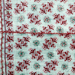 Four lengths of linen stitched together to make a panel. Embroidered in red silk and gold metallic threads on an unbleached linen ground. Pattern of diagonal floral crosses alternating with rosettes; the crosses alternate direction with each row. With a geometric floral border at the top and bottom. Silk embroidery in counted stitches: double running, stem, and long-armed cross. Stitches using metallic yarn: chain and overcast loop.