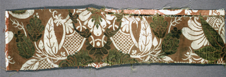 Fragment of russet silk satin brocaded in gold, and ivory and green silk, showing incomplete symmetrical  pattern of foliage and lattice. One selvage present.