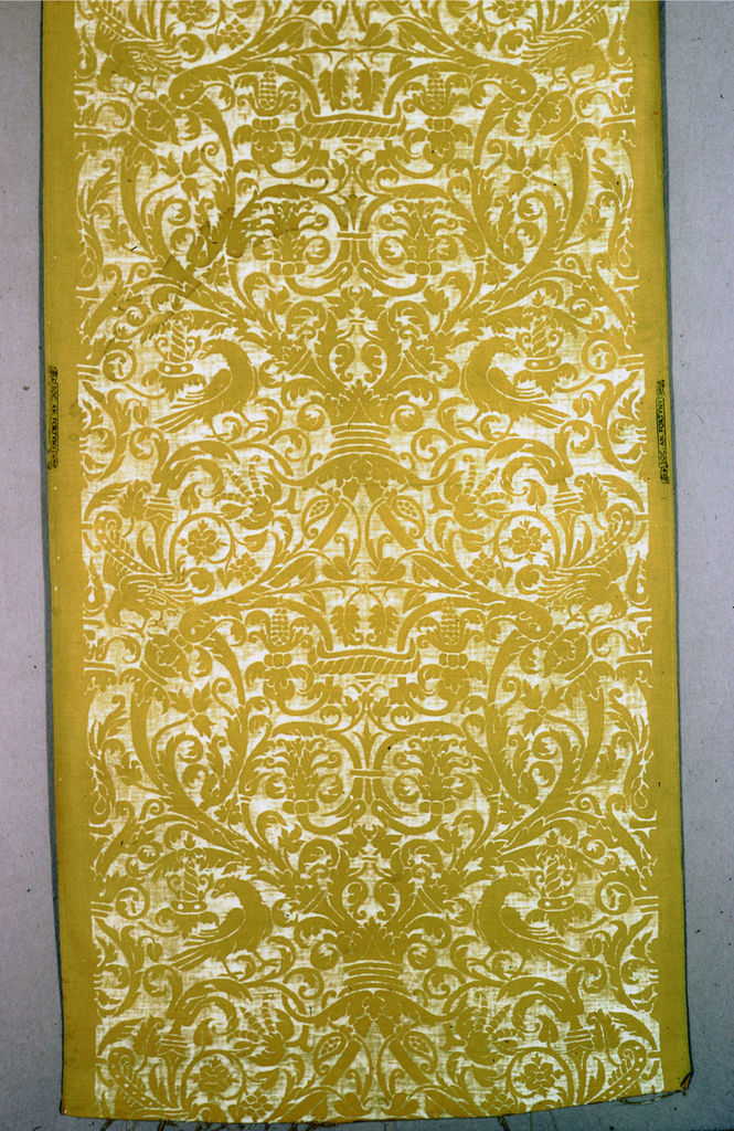 "Sixteenth century pattern in entwining plant forms,crowns, and birds in white on a yellow ground. Patterned named ""Uccelli"" is symmetrical with line of fabric."