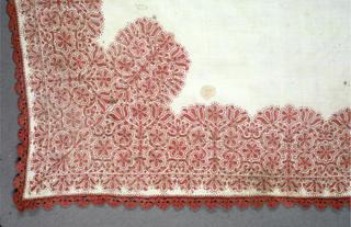 Embroidered pattern of tightly compacted scrolling vines and flowers in red silk on a ground of white linen. Pattern forms a border around the edge of the square with additional ornament in each corner. Square has a border of bobbin lace in the same silk as the embroidery.