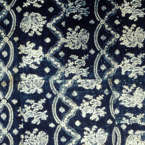 Blue resist on an ivory ground in a pattern of swag stripes alternating with stripes of detached flowers.