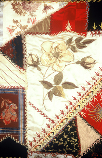 Patchwork cover made from a variety of woven fabrics and ribbons. Diamond shape in the center with a triangle on each side to form a central square surrounded by twelve squares plus an outer border. Each square contains an embroidered naturalistic flower.