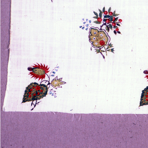 Printed cotton with a straight repeat of four offset, slightly dovetailed rows of  flowers, a different flower in each row. The flowers, in black, blue, green, yellow and red, are widely spaced on the white fabric.