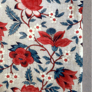 Fragment of printed cotton with a half-dropped repeat of a curving vine with large blossoms in black, blue and two reds on a white ground with black picotage.