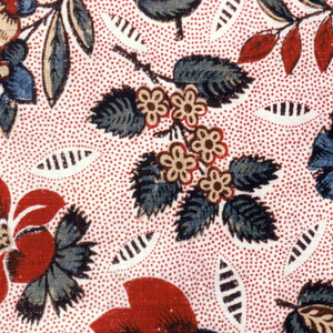 Half-drop repeat of flower blossoms, leaves and seed pods in bright colors heavily outlined in black on a white ground with red picotage.