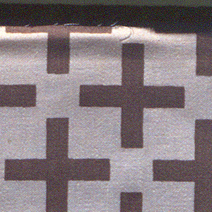 Brown plus signs printed on off-white ground in off set rows. Serged on two sides and cut on two sides.