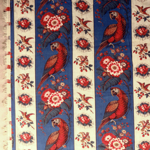 Unlined bed cover made of two full widths of printed fabric with fringe on four sides. Pattern composed oftwo stripes: the wider  a parrot holding a nut perched on a curved flowering branch on a blue background 18.5cm. wide and the other 11cm. wide a bird with outspread wings perched on a branch of red berries alternating with a ribbon bow. Two groups of stripes are half dropped with one extra marrow stripe plus an additional section of each stripe on left and right to fill full width of fabric.