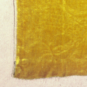 Slightly more than one repeat of a flower on a long curved stem with leaves within a symmetrical frame in the style of the 1st half of the 18th century. The pattern stamped in the strong yellow wool pile which is very stuff and long. (Pattern can be seen clearly on the back.)