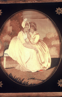 Mourning picture of two women seated on a bench in a landscape embroidered and painted in pastel colors; some use of chenille yarns. Framed with black eglomisé glass in oval shape.