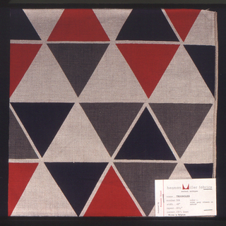 Row of triangles printed in grey, red and navy on tan. Serged on two sides, cut on two sides.