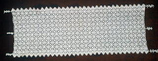 Square grid in which a four pointed star and rosette alternate. They are bobbin lace made to look like gauze. Three knotted tassels are at each end. Intended to look like reticella.