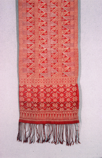 Long and narrow red silk selendang (shoulder cloth) with silver and gold geometric patterns. Field shows alternating pattern of vertical stripes with triangles and small eight-pointed flowers. A wide band at both ends with an eight pointed-flower within a diamond pattern followed by a thinner band patterned by triangles. Warp fringe tightly plied at both ends.