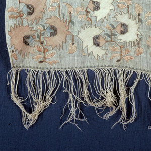 Towel with a wide border at each end. The border has three repeats of a five inch plant in shades of pink, blue and metallic silver. There is a five inch fringe at each end made from the warp.