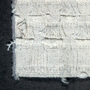 Off-white sample with an offset square pattern of cut floats of supplementary wefts (corduroy technique).