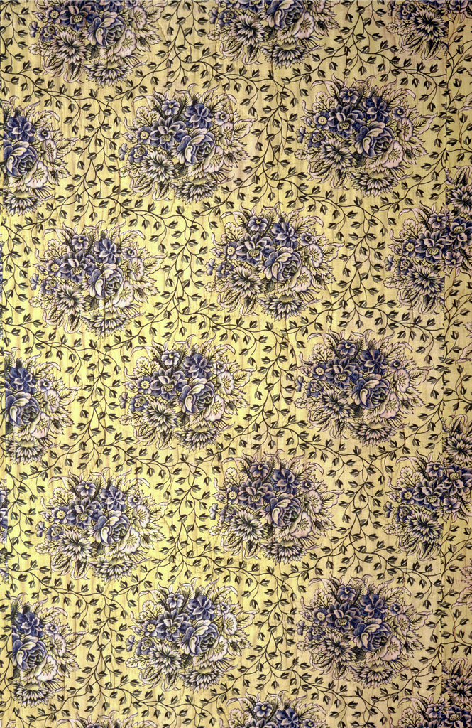 Piece of a quilted bedcover with right and bottom edges cut. Quilt top is made of four widths stitched together. Design has offset rows of a floral medallion enclosed in a fine vine in blue on a yellow background. Running stitch using cotton thread.