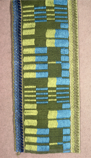 Wide green band patterned by green and blue rectangles formed by floats. Sewn to both sides is a three-quarter inch tape: green on one side and blue on the other.
