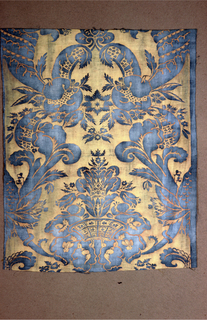 Large scale formal pattern symmetrical on the vertical centerline with large leaves and a basket in blue on a yellow background. Length of repeat is complete.
