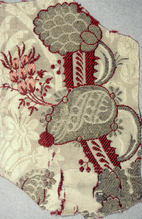 Fragment of ivory damask weave silk brocaded in silver yarns, with red and pink silk, showing floral design in the 'bizarre' style.