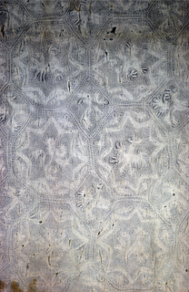 Octagon and diamond grid covering entire surface of half a quilt. Each diamond contains a four-legged animal: one with large antlers, another with a bird perched on its back. Each octagon has an eight-pointed star containing fantastic animals of various types with wings, antlers, tails; some are four-legged and others are bird-like. Weft-loop fringe on three sides.
