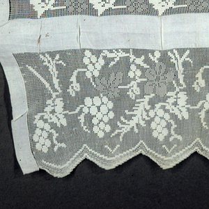 White towel with openwork floral-patterned bands at both ends. Inner band is narrow and patterned with alternating grape and leaf pattern while the outer band is wider with grapevines and flowers. Outer edge is scalloped.