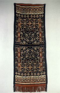 Woven textile (shoulder cloth) for ceremonial dress and decoration with European influenced design of floral arrangement. Features row of white triangles with figures inside. Fringed at one end.
