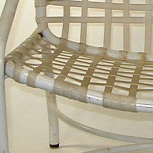 Round tubular aluminum frame and solid alumninum seating in vinyl lace.  Eight horizontal straps on back; thirteen are vertically oriented.  Two half ellipses of bent aluminum are placed back to back on the horizontal plane parallel to the chair's seat, serving as extra support for the chair's legs.  Rubber feet caps on each of four legs.