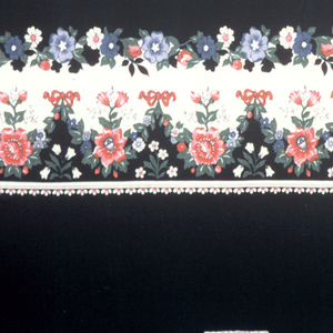 """Length of printed fabric with pattern """"railroaded"""" or printed parallel with the weft. Floral border at bottom with field above it patterned by half-drop clusters of roses on a black background. These border print designs appeared in fashion advertisements for Spring 1977 and were used primarily for skirts."""