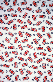 """Commemorative textile for the Silver Jubilee of Elizabeth II of Great Britain. Red and blue Union Jack flags and numerous """"Rs"""" are scattered over a white ground . The letter """"R"""" has a serif that terminates in a Tudor rose."""