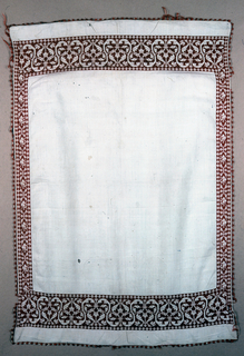 Towel with an embroidered end and side borders in red. The embroidery fills the background of the pattern in a pattern of a curving vine. Decorative silk fringe sewn to four sides in red and white block pattern.