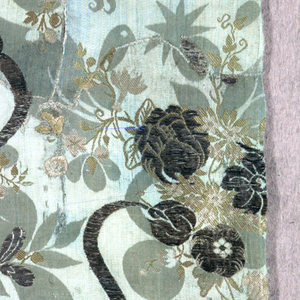 Fragment composed of many pieces sewn together. Light blue damask weave silk brocaded with metallic yarns showing design of fruits and florals with long curving stems in the 'bizarre' style.