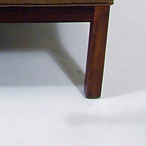Padded rectangular backrest cushion in same silk fabric as upholstered seat.  Straight legs, breadth of placement tapering towards back of chair.  Armchair sides flare, moving down from the top of the seat back and outwards towards the front of the chair, forming L-shaped armrests.  Rosewood frame visible at chair's base, but covered in green upholstery.