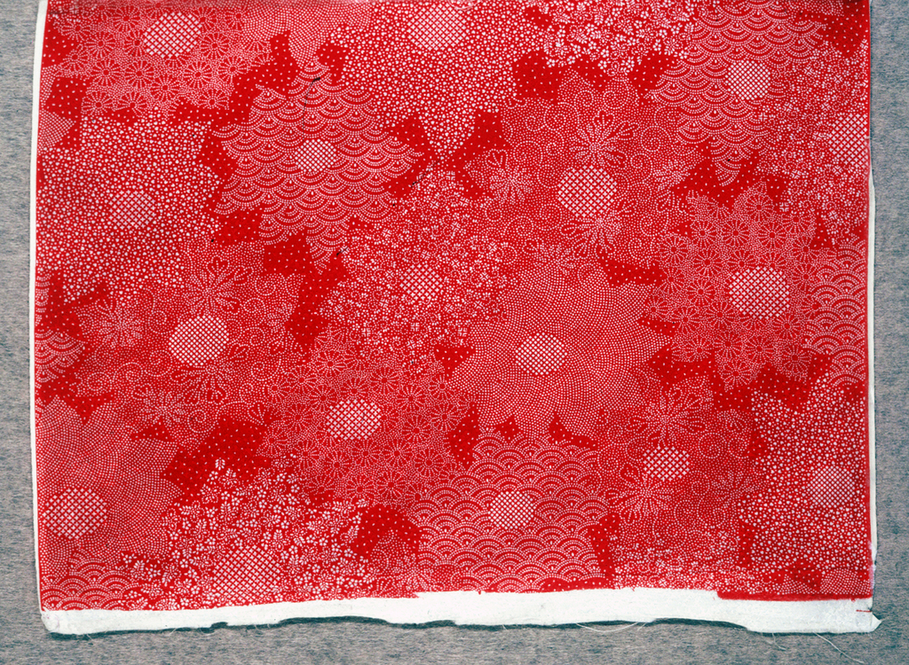 Less than one repeat of an allover pattern of flowers composed entirely of tiny punched shapes (Tsuki-bori). Reserved on red.