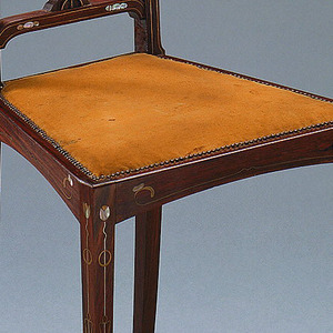 Small side chair with four slender tapered square legs; back consisting of low cross rail, narrow center splat and side rails with abrupt outward curve at top, repeated in crest rail where three large disks are centered.  Mother-of-pearl inlay; brass and white metal stringing on most elements.  Applied fruitwood cut out with brass stringing on center back splat; Seat upholstered in golden-yellow velvet.