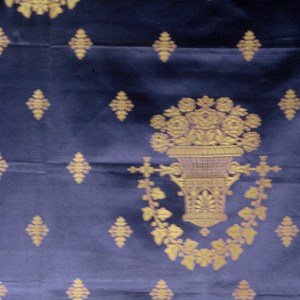 Baskets of flowers in acanthus swags and pointed rosettes in gold on blue. A companion design to 1979-9-8-a.