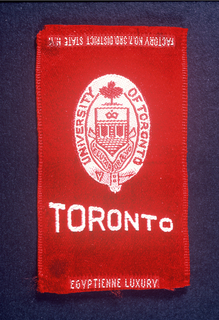 "Red woven cigarette silk from Egyptienne Luxury cigarette brand with ""Toronto"" and the seal of the University of Toronto in white."
