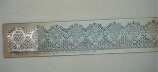 Pattern pricking with design drawn on green paper. Small sample of bobbin lace made from the pattern and sewn to the pattern.