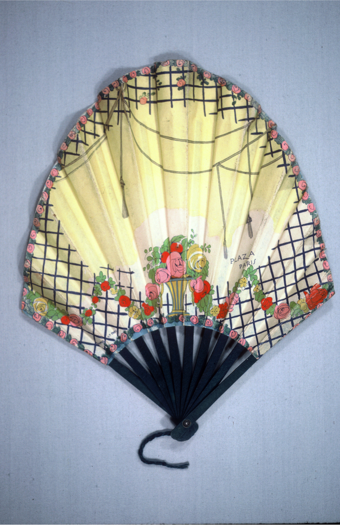 """Pleated fan with arched shape double leaf. Obverse: polychrome printed paper (possibly letterpress) with man and woman in eighteenth century costume in a garden attended by three servants. Reverse: printed paper with vase of roses surrounded by swags of roses and printed with advertising """"Plaza, Paris."""". Wood, sticks painted blue. Metal bail at rivet."""