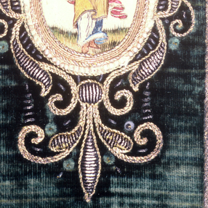 Book covered in green velvet with a central medallion embroidered in colored silks on white satin and enclosed by a ring of pearls within a heavy frame of metallic yarns, some raised. Different medallion on front and back.