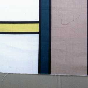 Length of printed fabric with a large-scale geometric design of vertical and horizontal bars in beige, teal and yellow with black outlines on an off-white ground.