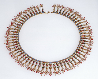 Gold and enamel necklace in the Hindu style with 100 cats-eyes, sixty-five cabochon rubies, 305 ruby beads set in sixty-five pendant motifs each with five pearls in gold tasseled ornaments.