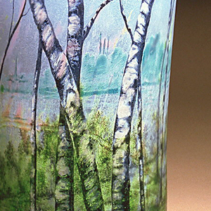 Tall vase with flared concave sides, decorated with enameled naturalistic birch trees on green foliage against a blue translucent sky spotted with pink.  Relief carving enhances the trees and foliage.