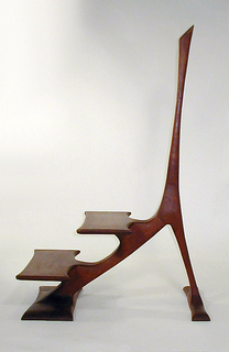 """Central support in the form of an inverted """"Y""""; from its longest arm projects two steps. Each arm rests on a flat rectangular platform. The whole executed in organic, free-flowing curving shapes."""
