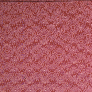 Length of fabric with a dyed red ground and white resisted design of small lozenges made up of dots.